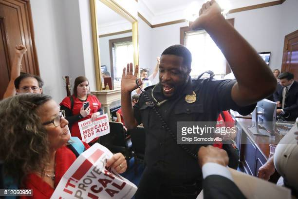 S Capitol Police officer forces demonstrators from Texas out of the offices of Sen Ted Cruz during a protest against health care reform legislation...