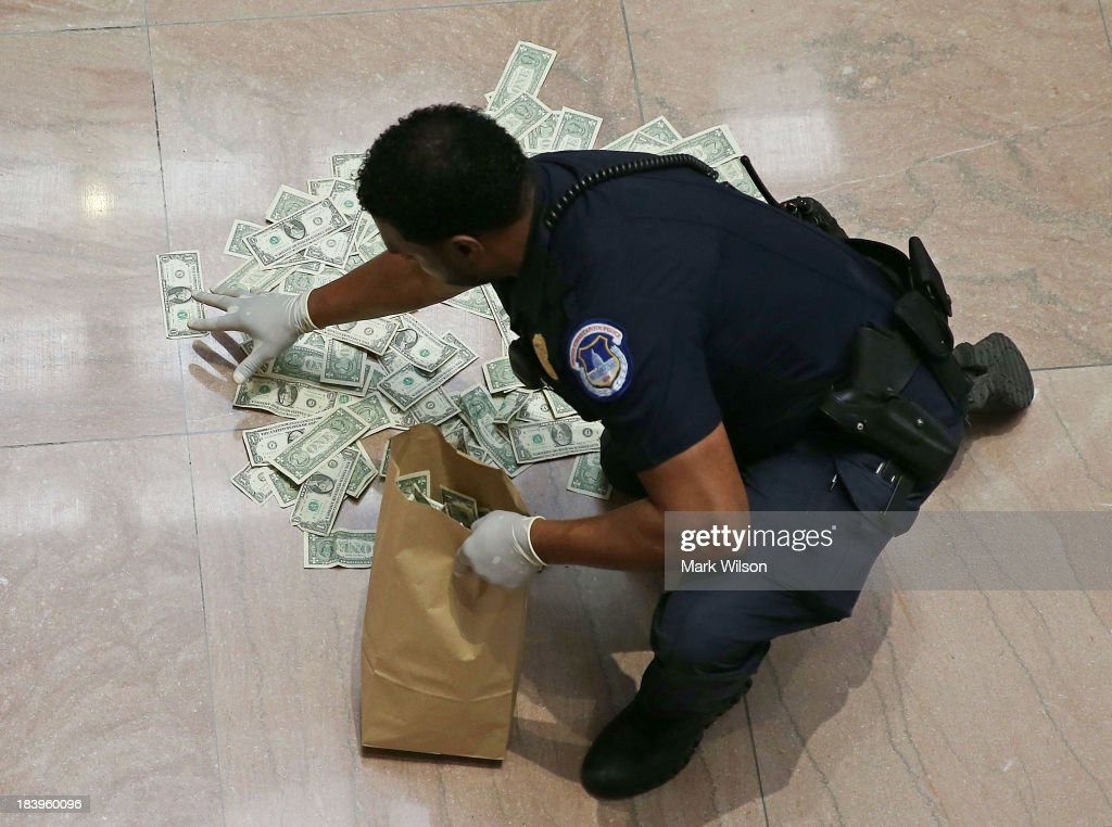 S. Capitol Police officer picks up money that was thrown on the floor by activists protesting against the government shutdown at the Hart Senate Office building, October 9, 2013 in Washington, DC. The U.S. government shutdown is entering its tenth day as the U.S. Senate and House of Representatives remain gridlocked on funding the federal government.