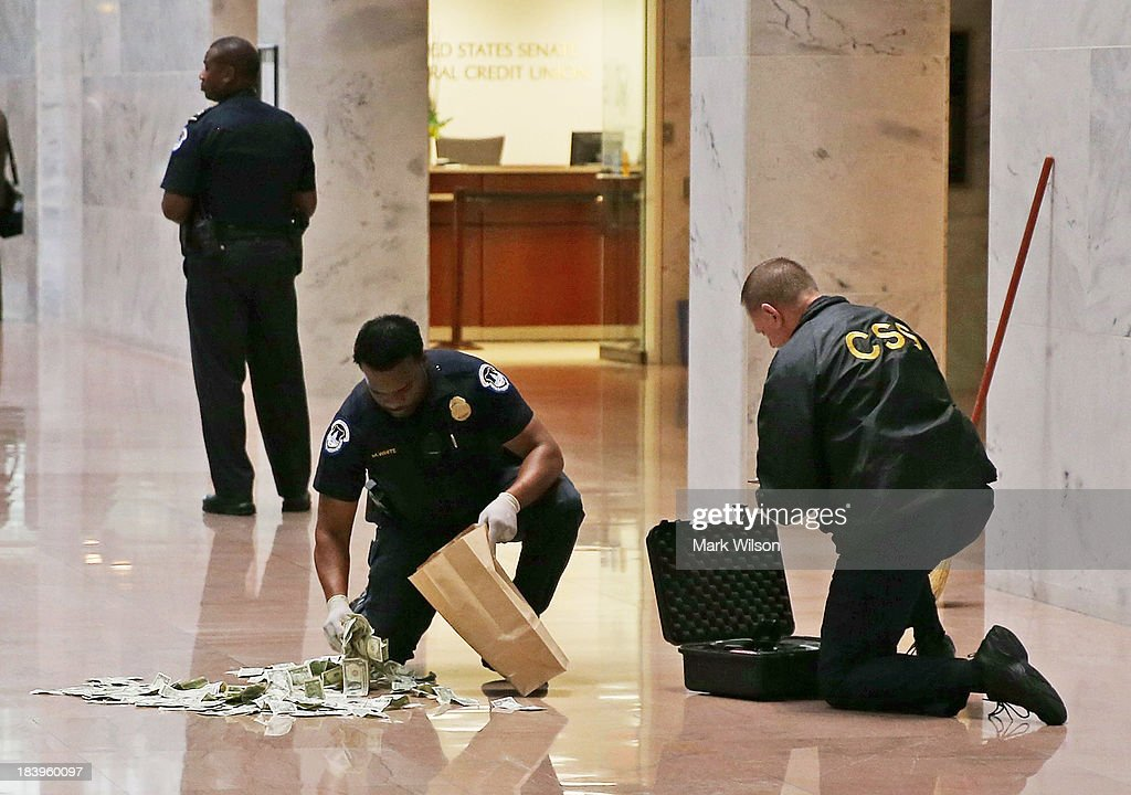 S. Capitol Police officer picks up money that was thrown on the floor by activists protesting against the government shutdown, at the Hart Senate Office building, October 9, 2013 in Washington, DC. The U.S. government shutdown is entering its tenth day as the U.S. Senate and House of Representatives remain gridlocked on funding the federal government.
