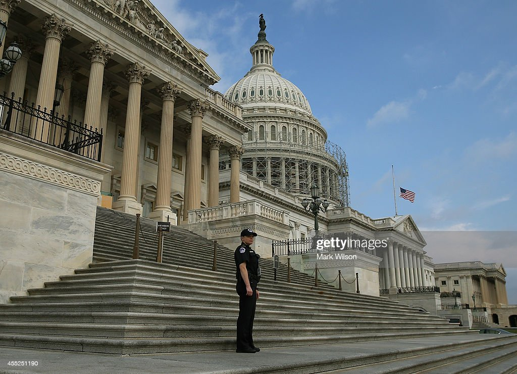 Capitol Police officer stands guard in front of the US Capitol building as the American flag flies at half staff September 11 2014 in Washington DC...