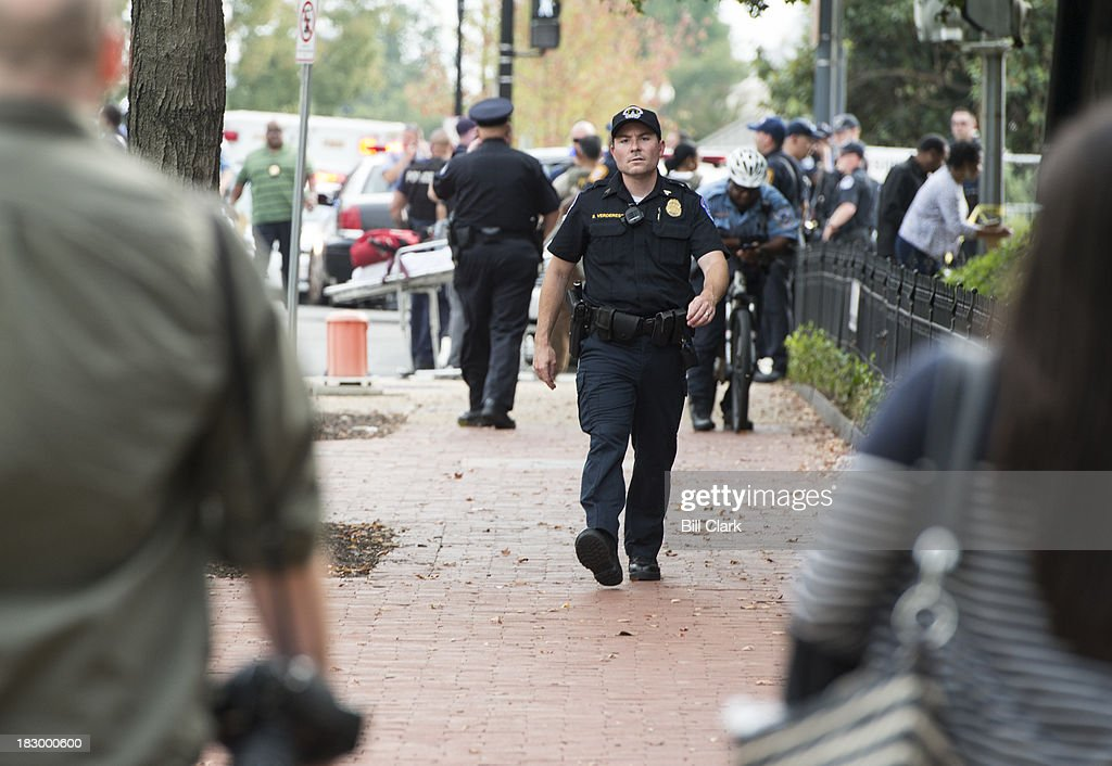 A Capitol Police officer stops media from walking to the scene of the shoot outside of the Hart Senate Office Building on Capitol Hill on Thursday, Oct. 3, 2013.