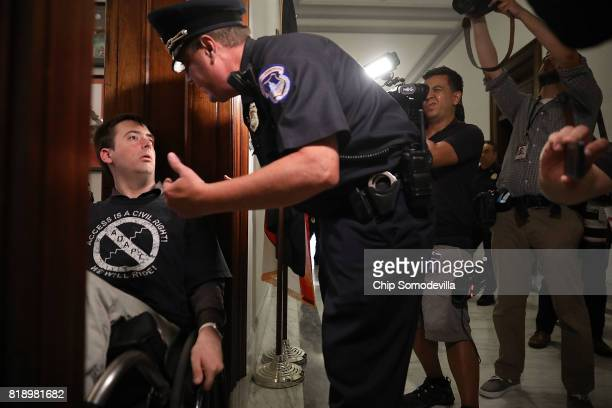 S Capitol Police officer talks with Nick Holzhum as he blocks the doorway to the offices of Sen Marco Rubio while protesting against the Republican...
