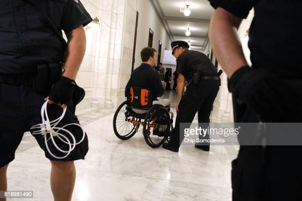 S Capitol Police officer talks with Nick Holzhum before he is arrested outside the offices of Sen Marco Rubio while protesting against the Republican...