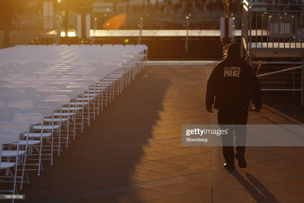 A U.S. Capitol police officer walks next to chairs placed in front of the Capitol building ahead of the presidential inauguration in Washington, D.C., U.S., on Sunday, Jan. 20, 2013. As he enters his second term U.S. President Barack Obama has shed the aura of a hopeful consensus builder determined to break partisan gridlock and adopted a more confrontational stance with Republicans. Photographer: Victor J. Blue/Bloomberg via Getty Images