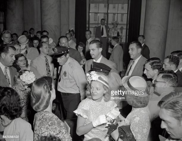 A US Capitol policeman leads plane builder Howard Hughes and an unidentified body guard through the record crowd that jammed the State Caucus room to...