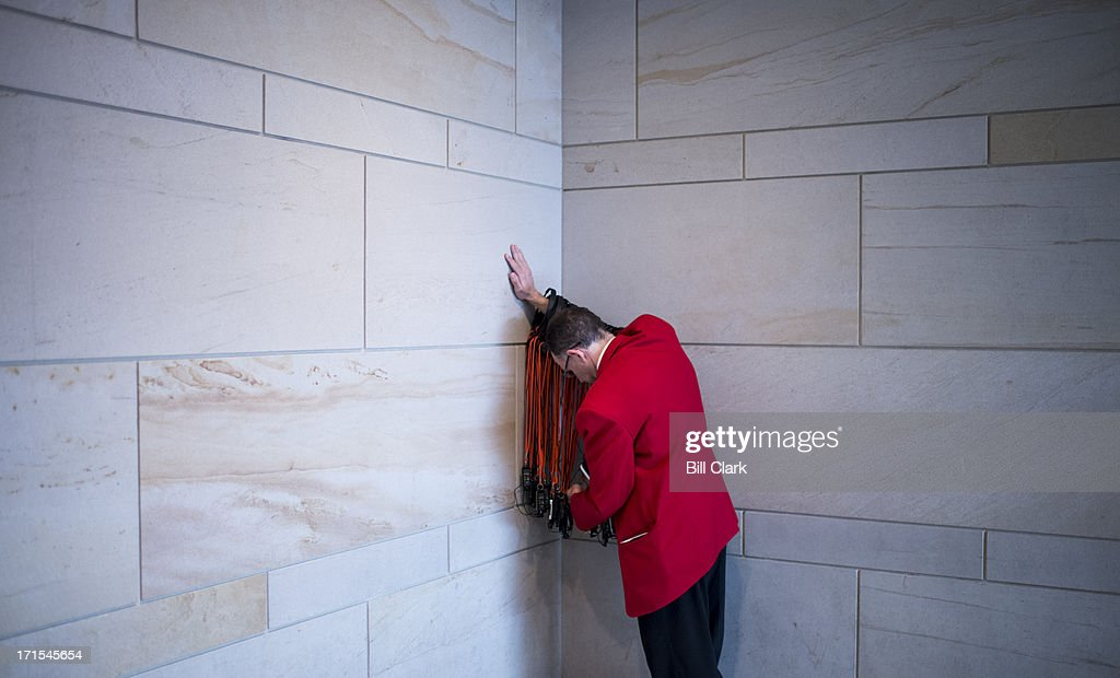 A Capitol Visitor Center employee leans against a wall as he untangles head sets in the CVC on Wednesday, June 26, 2013.