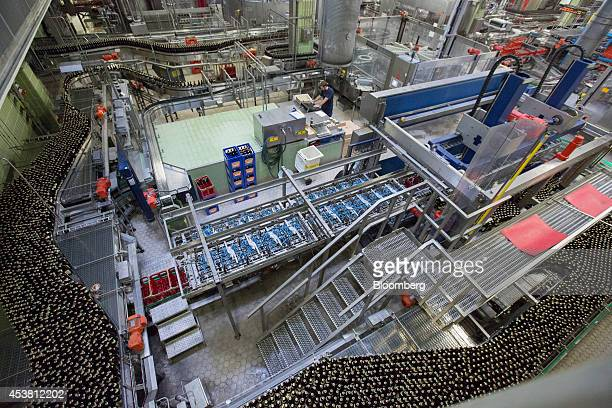 Capped bottles of beer pass along the production line at the Paulaner Brauerei GmbH brewery in Munich Germany on Monday Aug 18 2014 Though Germany...