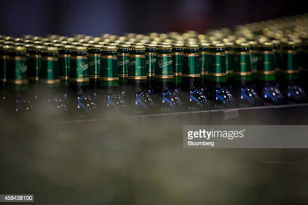 Capped bottles of Staropramen beer move along the production line at the Pivovary Staropramen AS brewing company operated by Molson Coors Brewing Co...
