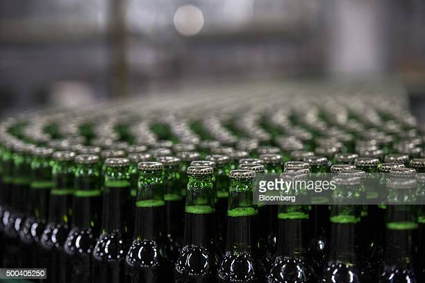 Capped green bottles of beer move along conveyor belts on the automated production line at the Pilsner Urquell brewery operated by SABMiller Plc in...