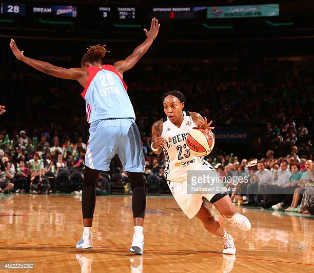 Cappie Pondexter of the New York Liberty drives past Sancho Lyttle of the Atlanta Dream during a game at Madison Square Garden in New York City on...