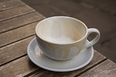 close up of cappuccino cup and saucer that have been used.