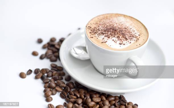 Cappuccino in white cup with coffee beans