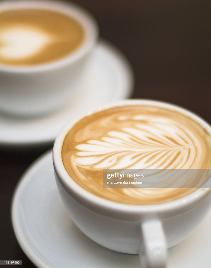 Cappuccino - One cup with decorated foam and bokeh background : Stock Photo