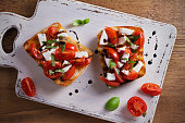 Caprese Bruschetta on white rustic chopping board. Tomatoes, basil, mozzarella cheese with balsamic sauce on toast. Antipasto - starter dish. overhead, horizontal