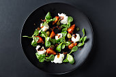 Caprese salad with mozzarella, tomato, basil and balsamic vinegar arranged on black plate and dark background. Top view.