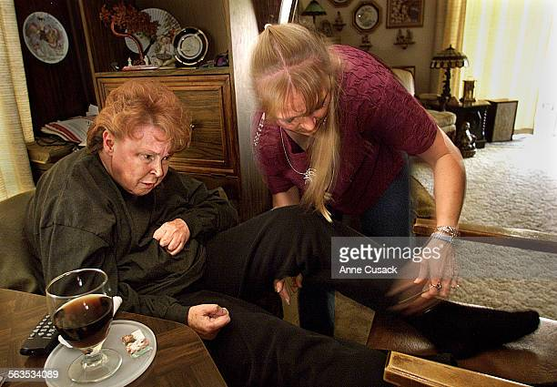 Caprice Kelton age 40 carefully adjusts the leg of her mother Judy Bonham age 63 who suffers from Multiple Sclerosis in their modest Camarillo home...