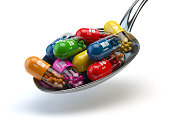 Capsules and pills on the spoon, isolated on white. Dietary supplements. 3d