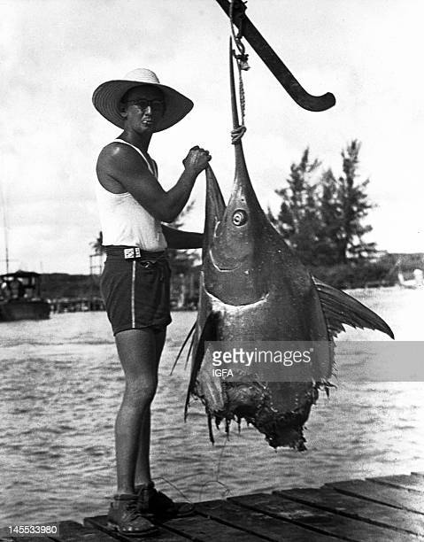 Capt Bill Fagen standing with a mutilated blue marlin on a dock around 1930 The marlin was attacked by a shark before Fagen could get it into his boat