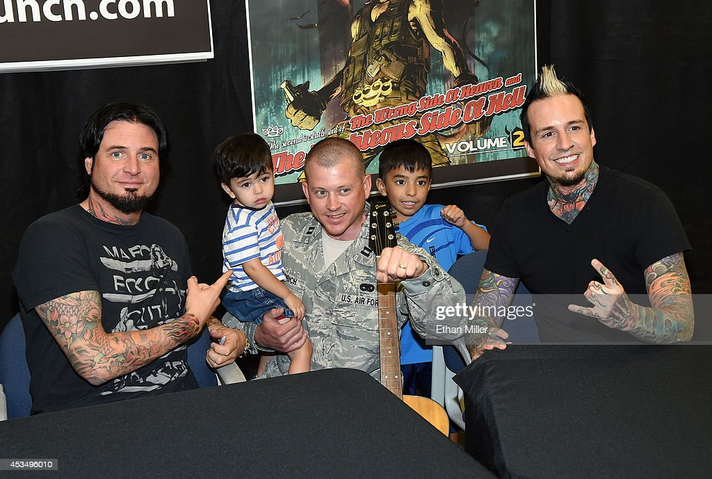Capt. Dan Gregorich (C) and his sons Danny Gregorich, 2 (2nd L), and David Gregorich, 6, pose with guitarist Jason Hook (L) and drummer Jeremy Spencer (R) of Five Finger Death Punch at Nellis Air Force Base as the band highlights its campaign to raise awareness about veterans suffering from post-traumatic stress disorder (PTSD), in part by launching the video 'Wrong Side of Heaven,' that deals with the subject on August 11, 2014 in Las Vegas, Nevada.