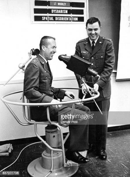 Capt James R Bridges of Warren Air Force Base Wyo sits in chair which was twirled to test his vertigo tendencies Second Lt Jack Whorley in charge of...