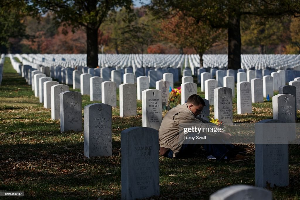 Capt. Jeff Cliffe, with the U.S. Marine Corps, sits next to the grave of his grandfather and grandmother on Veteran's Day at Arlington National Cemetery on November 11, 2012 in Arlington, Virginia. Numerous events are under across the country to honor the nation's current and former service members.