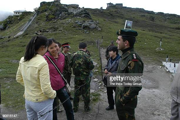 Capt Neetesh Sharma of the Indian army talks to Chinese civilian girls across the border fence at Nathu La as a Chinese civilian watches on Trade...