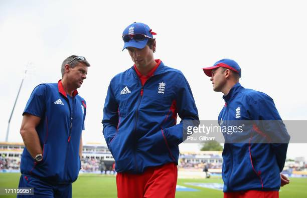 Captain Alastair Cook of England walks off following the 300pm pitch inspection as England coach Ashley Giles talks to Jonathan Trott during the ICC...