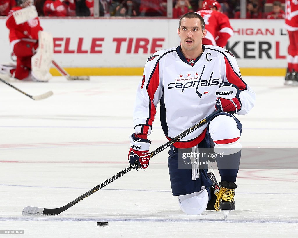 Captain Alex Ovechkin #8 of the Washington Capitals stretches on the ice during pregame warm-ups before an NHL game against the Detroit Red Wings at Joe Louis Arena on November 15, 2013 in Detroit, Michigan.