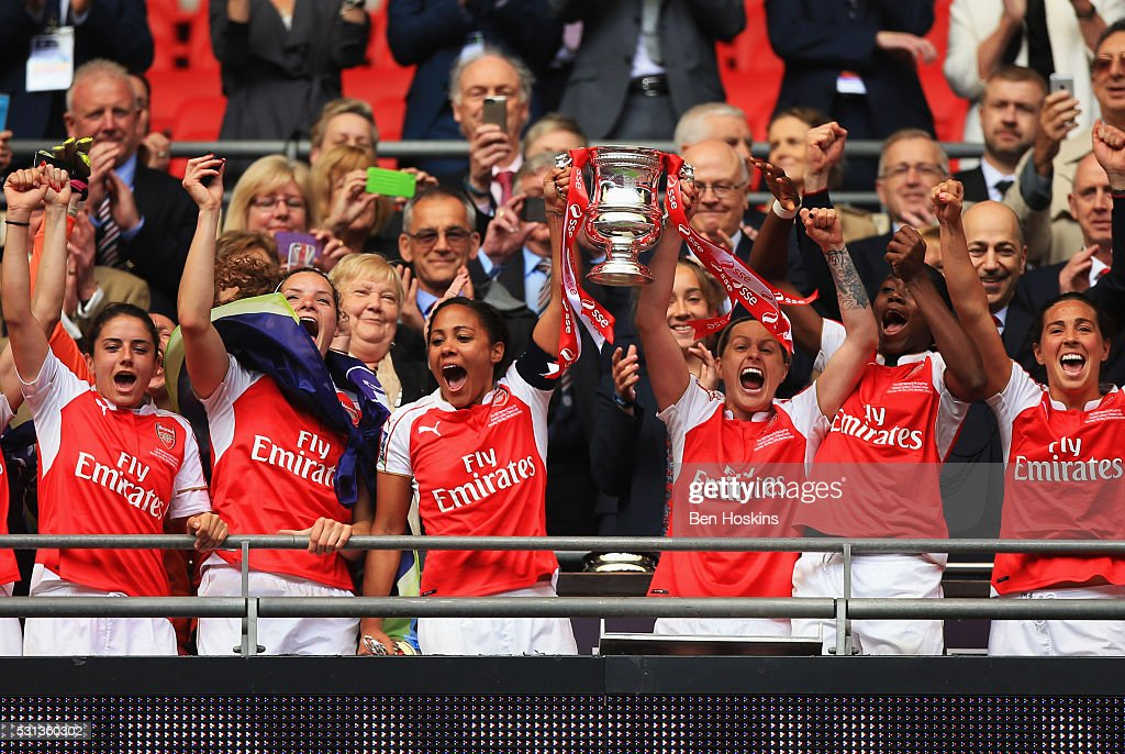 Captain Alex Scott and Kelly Smith lift the trophy with team mates as they celebrate victory after the SSE Women's FA Cup Final between Arsenal...