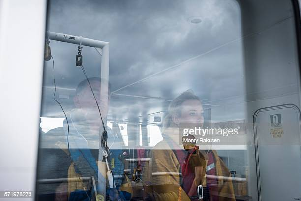 Captain and female scientist reflected in window on research ship