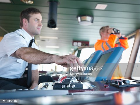 Captain and ship worker on ships bridge