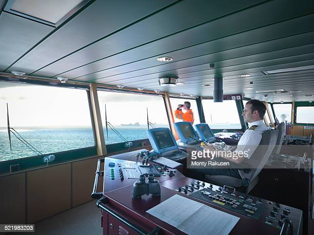 Captain and worker on bridge steering ship at sea