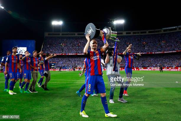 Captain Andres Iniesta offers the King's Cup to the audience after winning the Copa Del Rey Final between FC Barcelona and Deportivo Alaves at...