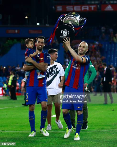 Captain Andres Iniesta offers the King's Cup to the audience ahead his teammate Sergio Busquets Burgos after winning the Copa Del Rey Final between...