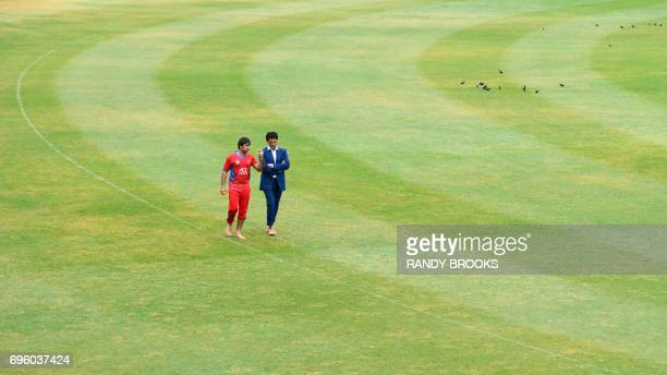TOPSHOT Captain Asghar Stanikzai and manager Shir Agha Hamkar of Afghanistan walk around the field as rain delays the start of the 3rd and final ODI...
