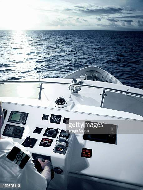 Captain at helm of large motor yacht