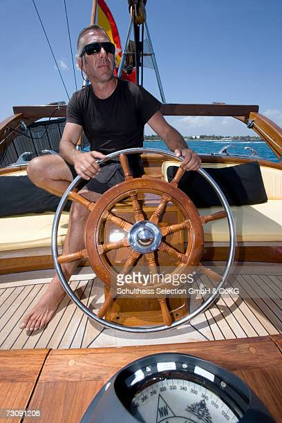 Captain at the helm of sailboat, compass in foreground