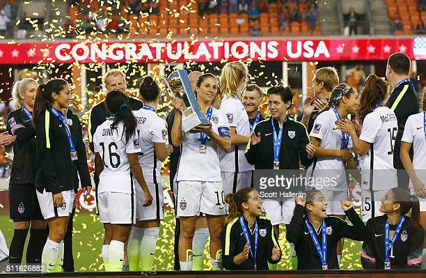 Captain Carli Lloyd poses on stage with members of the United States after they beat Canada 20 during the Championship final of the 2016 CONCACAF...