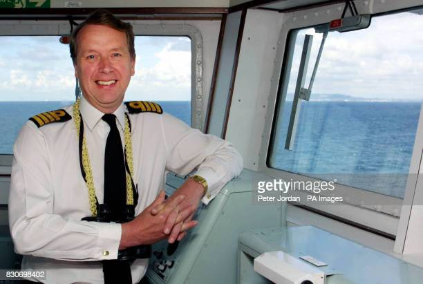 Captain David Snelson commanding officer of the Royal Navy aircraft carrier HMS Ark Royal on the bridge as she sails into Portsmouth harbour after a...