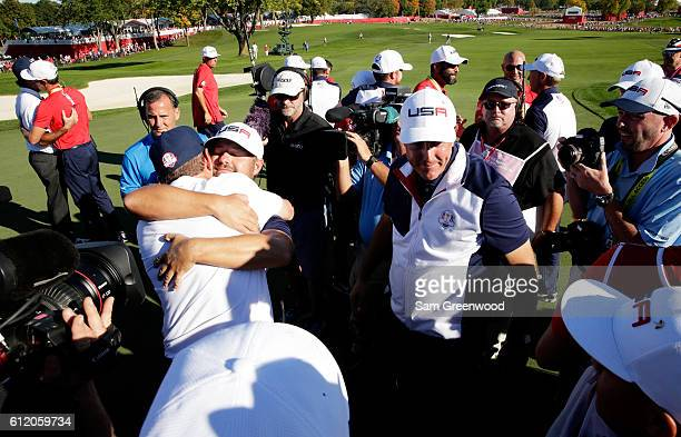 Captain Davis Love III of the United States celebrates with Ryan Moore and Phil Mickelson on the 18th green after winning the Ryder Cup during...