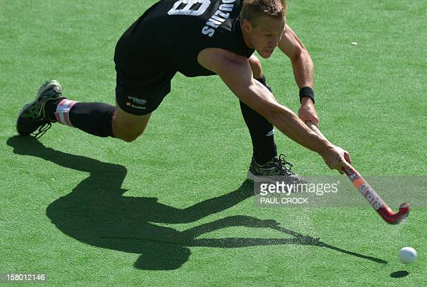 Captain Dean Couzins of New Zealand strikes the ball during the match against England at the men's Hockey Champions Trophy tournament in Melbourne on...