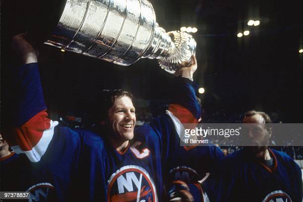 Captain Denis Potvin of the New York Islanders hoists the Stanley Cup as teammate Butch Goring looks on after winning the 1982 Stanley Cup Finals...