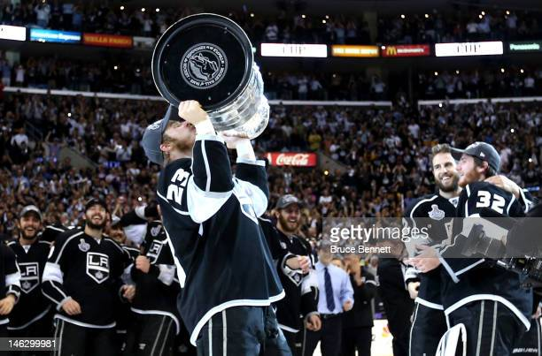 Captain Dustin Brown of the Los Angeles Kings kisses the Stanley Cup as Jonathan Quick and Simon Gagne hug after the Kings defeated the New Jersey...