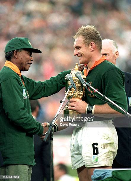 Captain Francois Pienaar of South Africa receives the William Webb Ellis Cup from the South African President Nelson Mandela after the Rugby World...