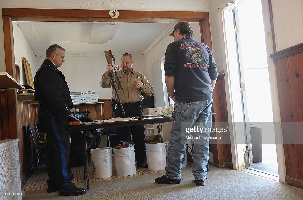 A Captain from the Keansburg Police Department (L) and a Firearms Instructor from the Monmouth County Prosecutor's Office (C) receive a firearm during a gun buyback program on March 9, 2013 in Keansburg, New Jersey. In a national effort to curb gun violence, the NJ Attorney General's Office in cooperation with the Monmouth County Prosecutor's Office held an anonymous buyback program where every gun turned in is to be melted down.