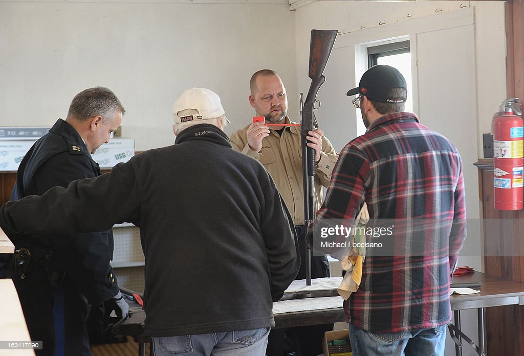 A Captain from the Keansburg Police Department (L) and a Firearms Instructor from the Monmouth County Prosecutor's Office (2nd R) receive a firearm during a gun buyback program on March 9, 2013 in Keansburg, New Jersey. In a national effort to curb gun violence, the NJ Attorney General's Office in cooperation with the Monmouth County Prosecutor's Office held an anonymous buyback program where every gun turned in is to be melted down.