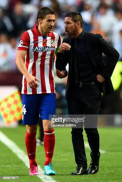 Captain Gabi of Club Atletico de Madrid speaks to Diego Simeone Coach of Club Atletico de Madrid during the UEFA Champions League Final between Real...