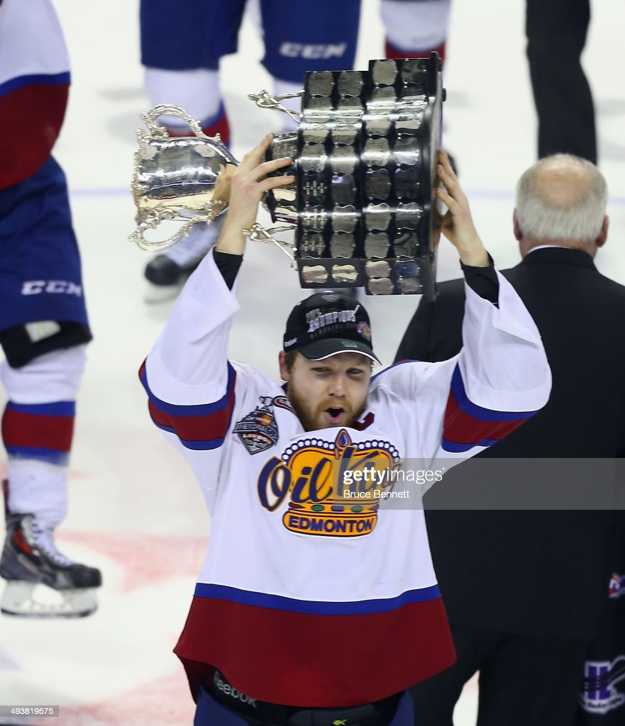 Captain Griffin Reinhart #8 of the Edmonton Oil Kings holds the Memorial Cup trophy following a 6-3 victory over the Guelph Storm in the 2014 Memorial Cup championship game at Budweiser Gardens on May 25, 2014 in London, Ontario, Canada.