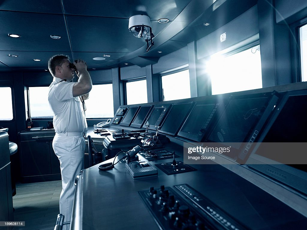 Captain in cockpit of motor yacht, using binoculars