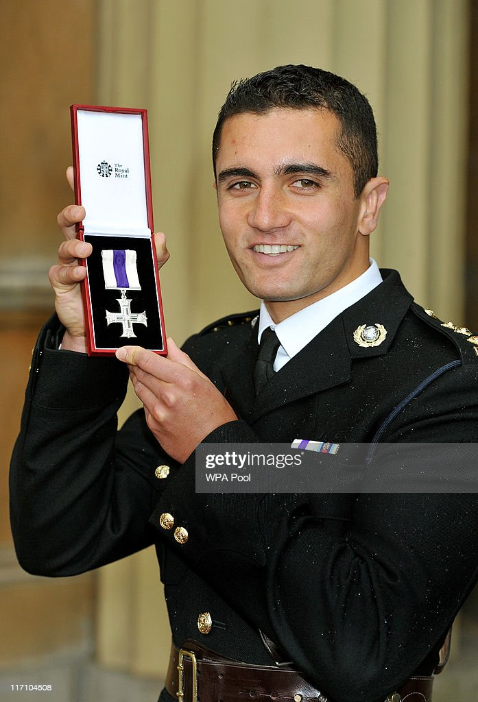 Captain Jack Anrude of the Royal Marines holds his Military Cross, after it was presented to him by the Prince of Wales, at the Investiture Ceremony on June 23, 2011 at Buckingham Palace, London.